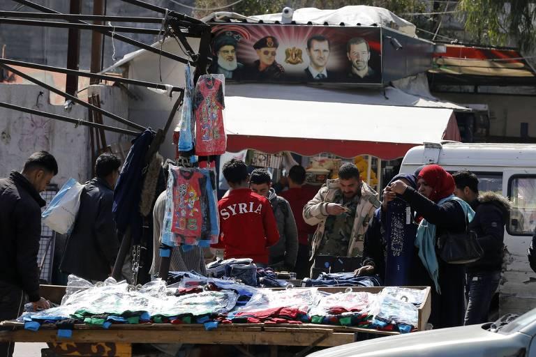 Sírios fazem compra em mercado de rua em Damasco; níveis de pobreza atingiu recorde