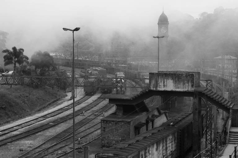 Foto em preto e branco de estação de trem sob névoa