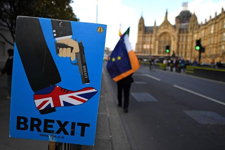 Cartaz contra o brexit é exibido durante protesto na frente do Parlamento britânico nesta quarta (27)