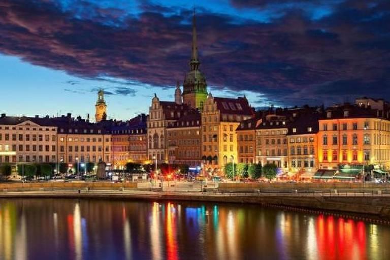 Cidade às margens de rio, iluminada