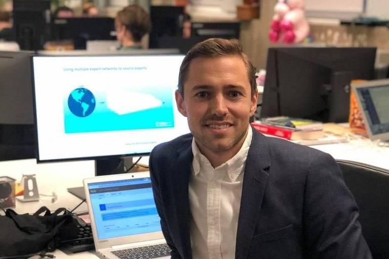 Homem com terno sentado em frente de computador