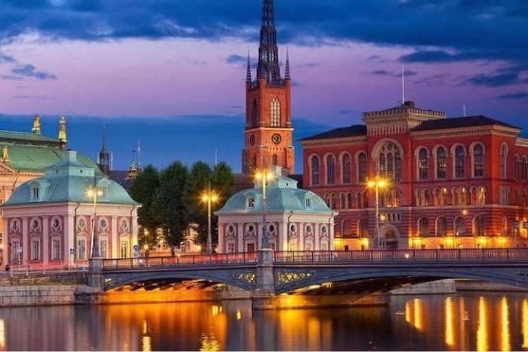 Cidade com ponte sobre rio, iluminada, à noite