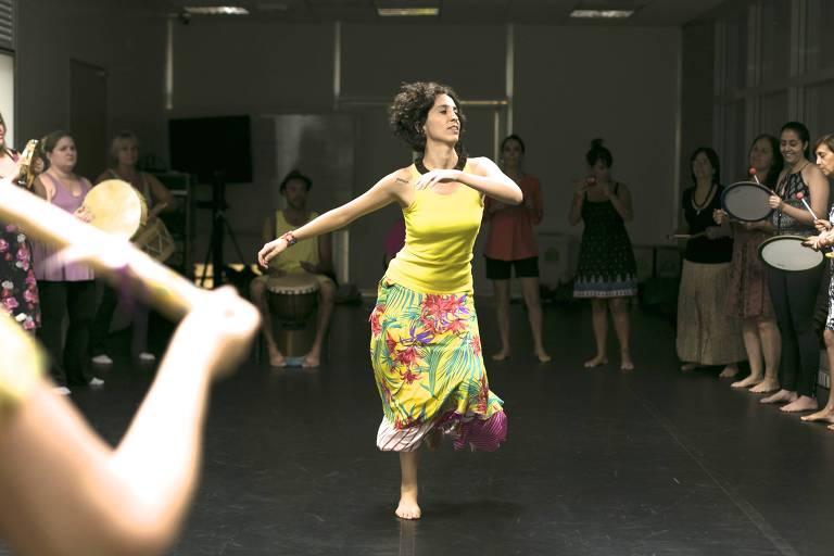mulher de amarelo dança em meio a roda de instrumentos musicais