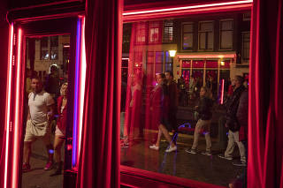 Visitors pass the room of a sex worker in the red-light district of Amsterdam.