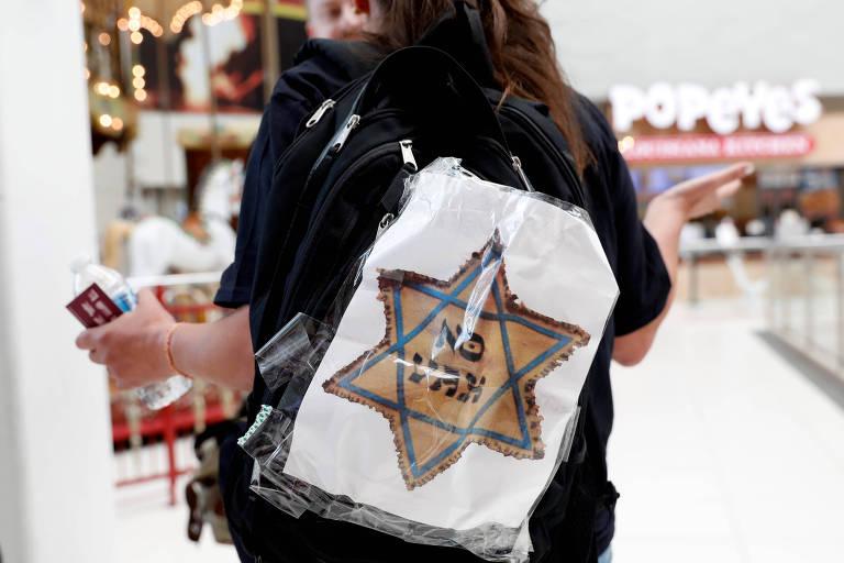 """Mulher que se opõe à vacinação de crianças com placa de """"No Vax"""" (não à vacinação, em tradução livre) no meio de uma estrela de Davi, símbolo judaíco"""