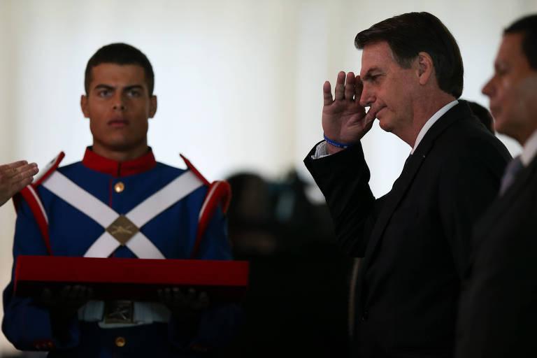 Bolsonaro presta continência ao lado do vice, general Mourão, em evento da Justiça Militar