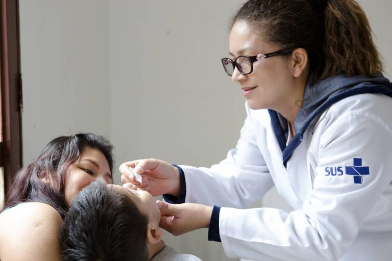 Mulher aplica gota de vacina na boca de uma criança