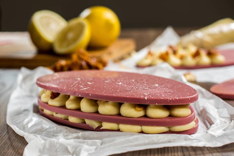 Um dos lançamentos da Cristallo três pedaços de chocolate Ruby cortados em formato oval e recheados com ganache de limão-siciliano e raspas de coco queimado