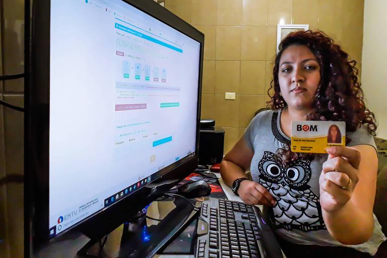 mulher de cabelos enrolados, em frente a um computador, segurando um bilhete BOM Escolar