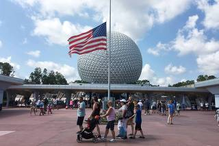 Visitors walk pass a Stars and Stripes flying half-staff at the entrance to the Epcot Center at Walt Disney World resort in Orlando