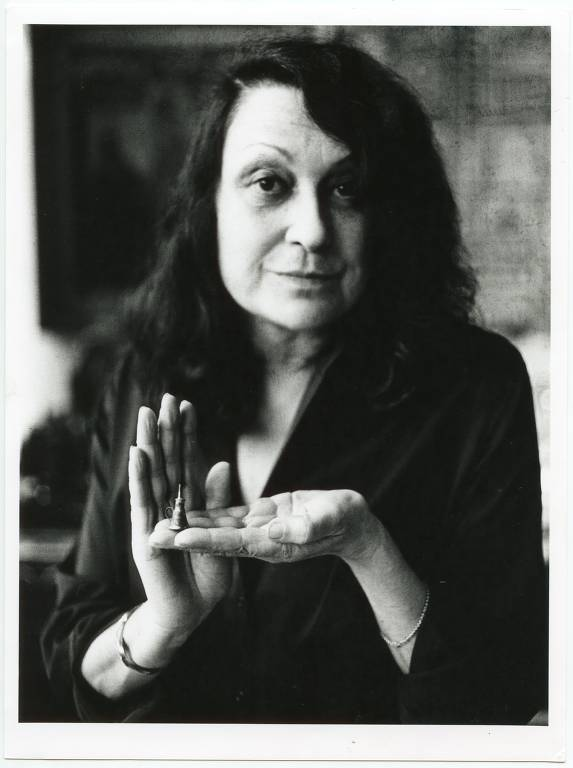 Arquiteta ítalo-brasileira Lina Bo Bardi; foto preto e branco mostra uma mulher de meia-idade com longos cabelos, segurando na palma da mão esquerda um minúsculo objeto, algo assim como um sininho, tão pequeno que ela quase o ampara com a mão direita aberta junto à esquerda