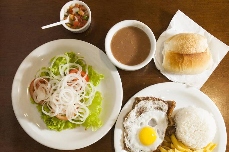 Pratos sobre uma mesa com tomate, feijão, salada