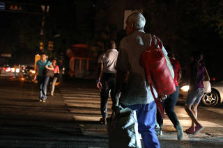 People cross a road during a blackout in Caracas, Venezuela