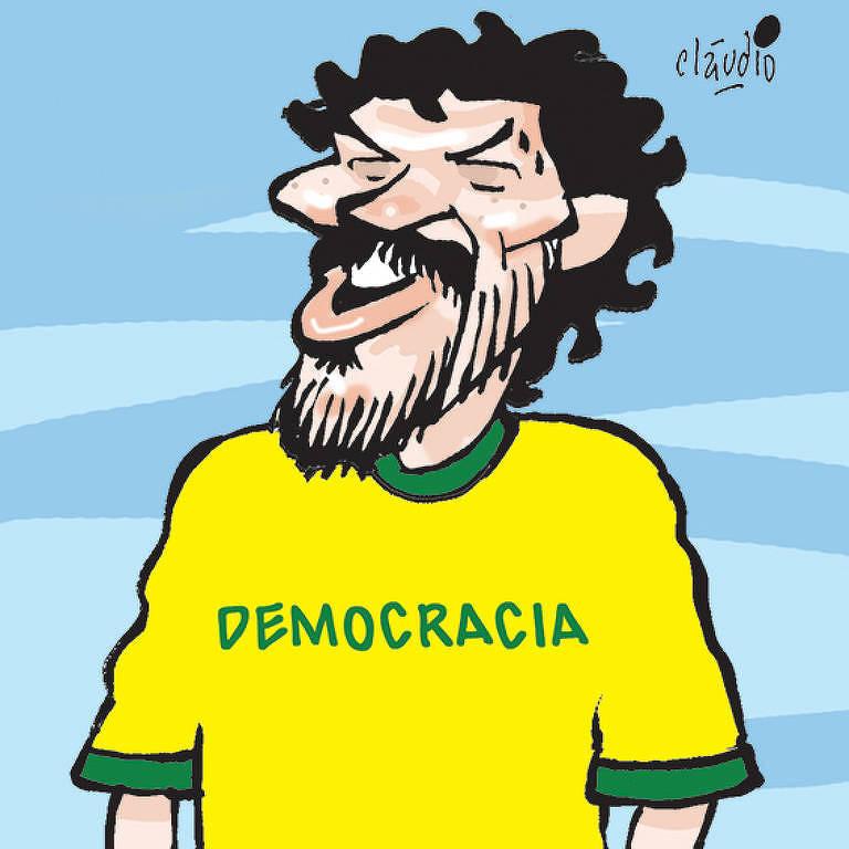 Ex-jogador corintiano Sócrates com camisa verde e amarela com a palavra Democracia
