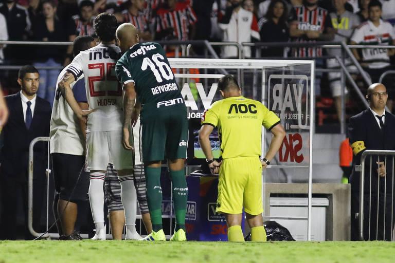 Jogadores do Palmeiras e do São Paulo aguardam enquanto o árbitro consulta o VAR em partida no estádio do Morumbi, em São Paulo