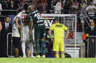 Hudson (São Paulo) e Deyverson (Palmeiras) observam árbitro, que revê lance do pênalti