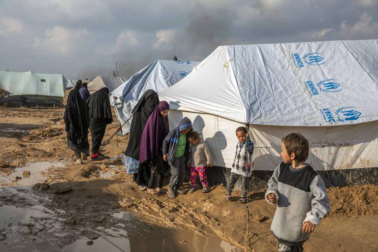 Caminho enlameado do campo Al Hol, na Síria, com mulheres e crianças que eram ligados ao Estado Islâmico