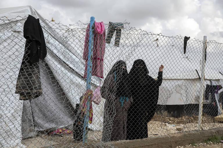 Mulheres cobertas por véu aguardam no campo