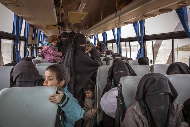 Mulheres e crianças cruzam o deserto em ônibus que têm como direção o campos controlados por milícias curdas