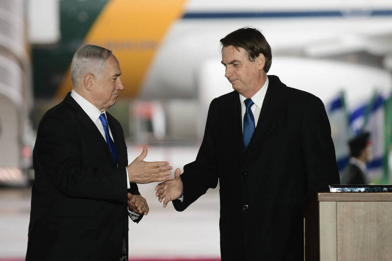 O presidente Jair Bolsonaro, à dir., cumprimenta o premiê de Israel, Binyamin Netanyahu, no aeroporto Ben Gurion, próximo a Tel Aviv