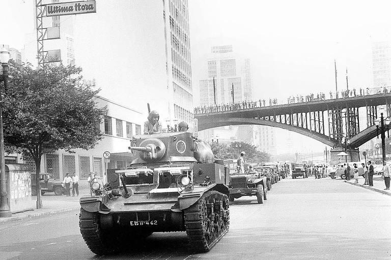 Na imagem em preto e branco, um tanques de guerra estão no meio de uma rua em meio a prédios