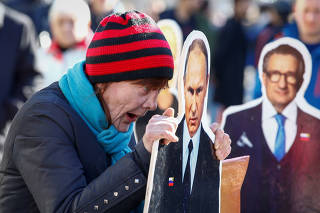 A woman reacts as she holds a cut-out figure depicting Russian President Vladimir Putin in Kiev