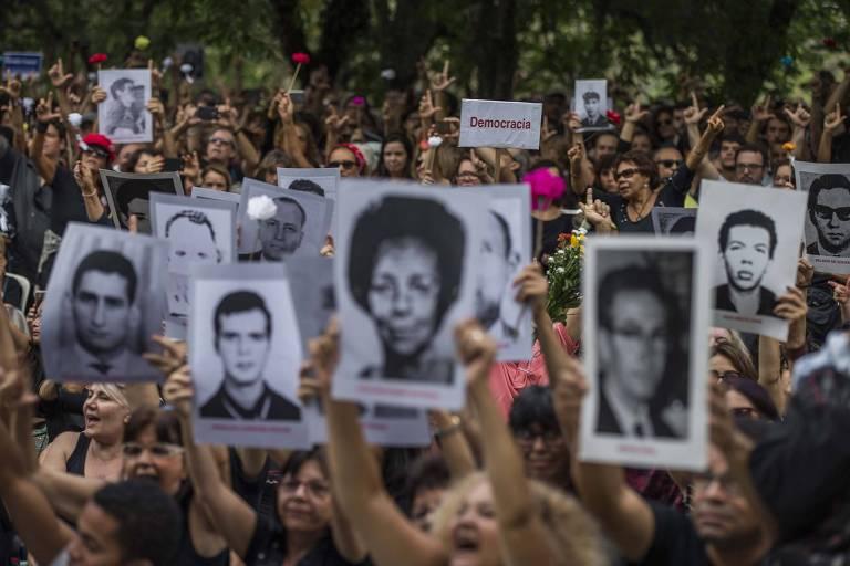 Em protesto contra o golpe de 1964, ativistas seguram fotos de mortos e desaparecidos políticos durante a ditadura