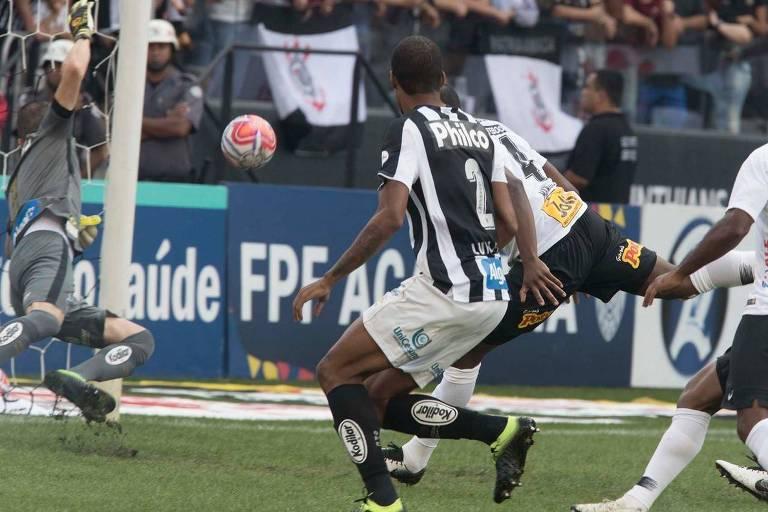 O zagueiro corintiano Manoel se atira para desviar a bola de cabeça e abrir o placar para o Timão contra o Santos, no Itaquerão