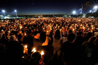 FILE PHOTO: People attend a candlelight vigil the day after a shooting at Marjory Stoneman Douglas High School in Parkland