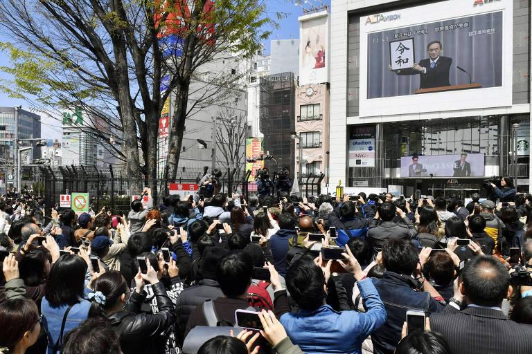 Público observa anúncio da nova era em um telão em Tóquio