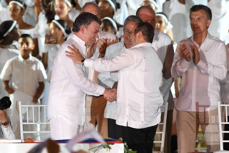O então presidente, Santos, e Timochenko, líder das Farc, celebram acordo