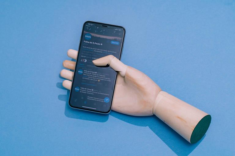 Mão de madeira segura smartphone