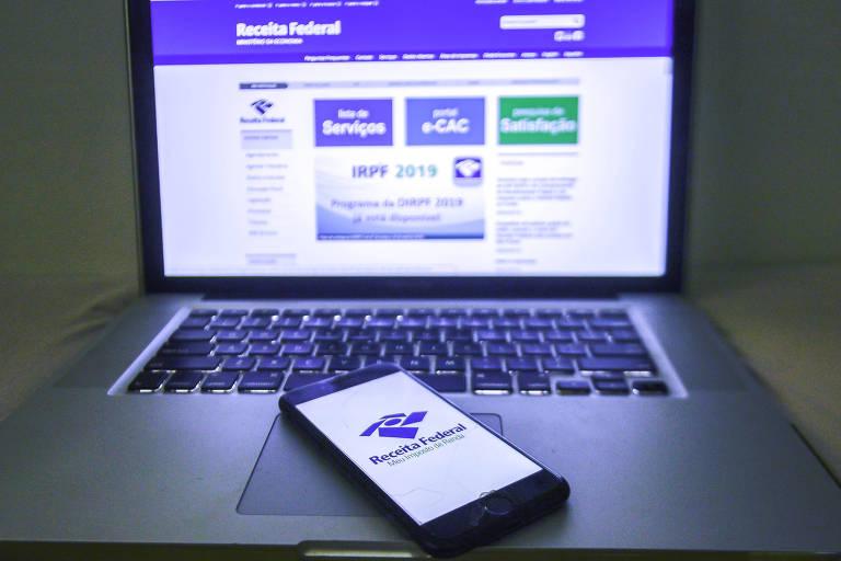 Computador e telefone celular mostram o site da Receita Federal