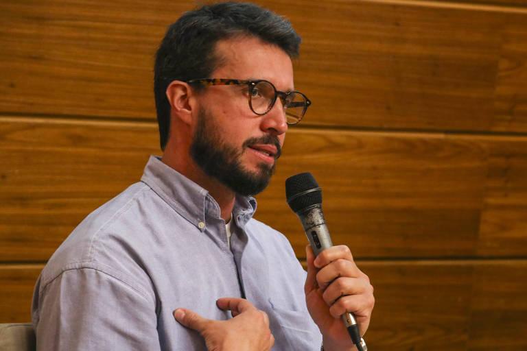 homem de barba e óculos fala ao microfone olhando para a direita
