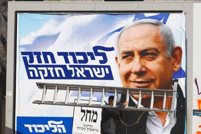 Homem passa por anúncio eleitoral com o retrato de Binyamin Netanyahu em Tel Aviv