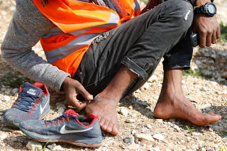 A man inspects his feet during a break after a walk on the highway near Amman during a march from the southern city of Aqaba south of the capital