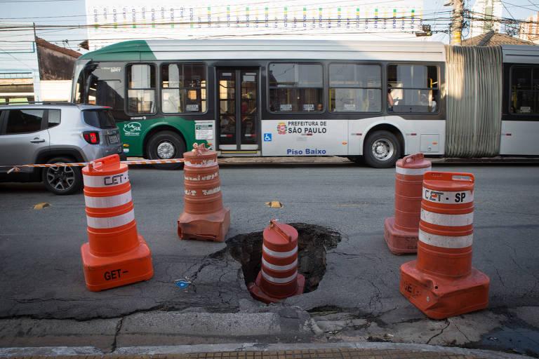 cone dentro de um buraco na rua com outros quatro cones em volta para alertar motoristas
