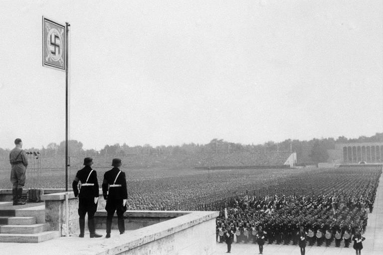 Adolf Hitler (no canto esquerdo) discursa para a militância nacional-socialista durante comício do Partido Nazista em Nuremberg, em 1937