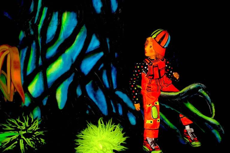 boneco com iluminação fluorescente em cena de peça infantil