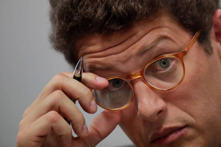 Ricardo Salles, ministro do Meio Ambiente do governo Bolsonaro, segura o óculos, aparentemente o arrumando no rosto; o ministro também tem uma caneta na mão