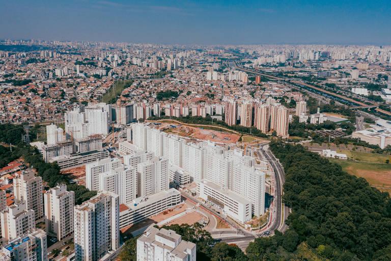 A foto mostra uma vista panorâmica, como se tirada de um drone ou helicóptero, mostrando todo o complexo da construção da MRV para o projeto Minha Casa Minha Vida. Os prédios do projeto são todos brancos e possuem árvores rodeando um dos lados.
