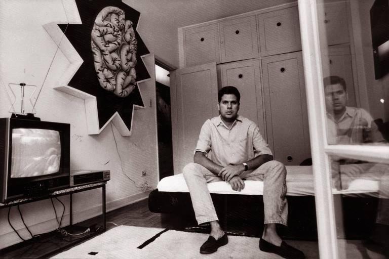 Foto de arquivo de arquivo, em preto e branco, do marchand e colecionador Marcantonio Vilaça sentado de pernas abertas em uma cama, em um quarto com uma televisão à direta, uma obra na parede acima dela e um armário ao fundo. Ele usa uma camisa polo, calça e um relógio de pulso.