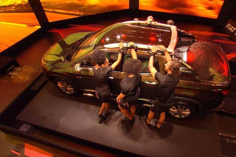 Com uma roupa preta e divididos em dois grupos, participantes do BBB 19 estão em pé com uma das mãos amarrada num Fiat Toro, prêmio para quem vencer a disputa