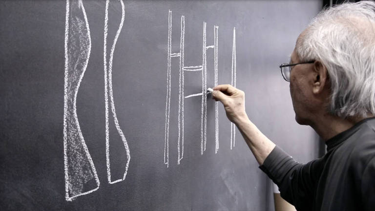 De costas, Ruy Ohtake desenha seus móveis com giz em parede de lousa.