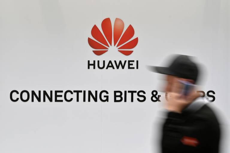 Homem caminha em frente a logo da Huawei
