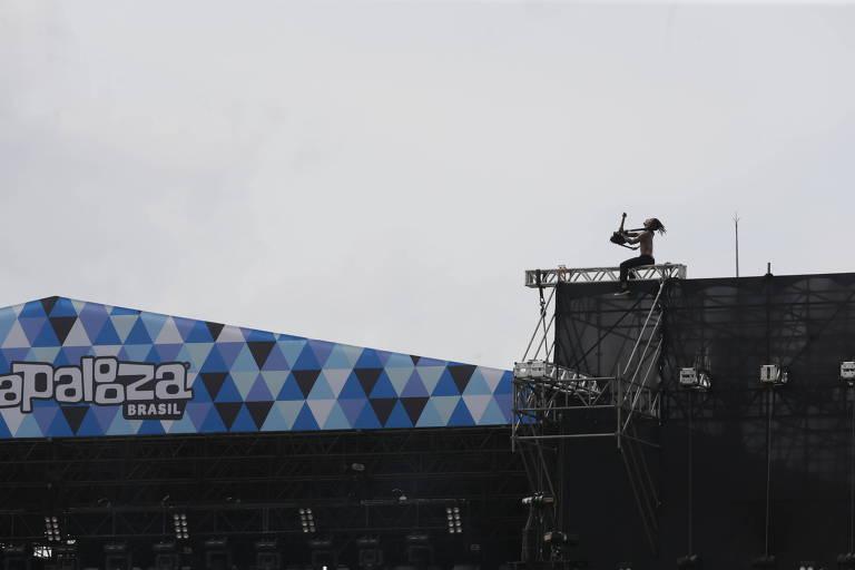 À esquerda na foto, Stephen Harrison, da banda Fever 333, toca sua guitarra sentado na estrutura de metal do palco Adidas montada no autódromo internacional de Interlagos para o Lollapalooza Brasil