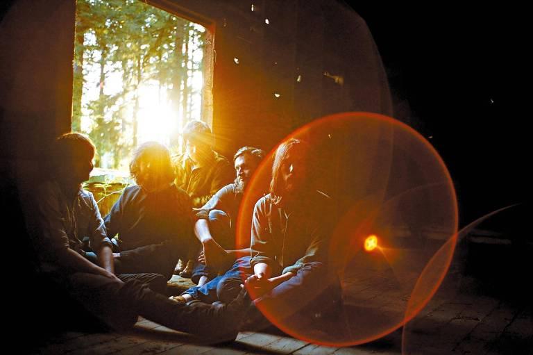 Em sala iluminada pelo pôr-do-sol, os quatro integrantes da banda Fleet Foxes sentam juntos no chão.