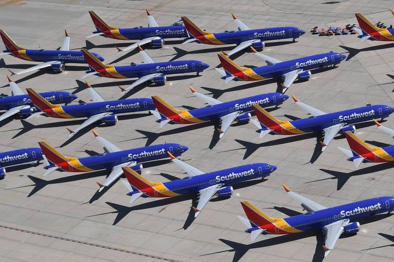 Vista panorâmica de diversos aviões azuis da Boeing, modelo 737 MAX, estacionados no aeroporto.