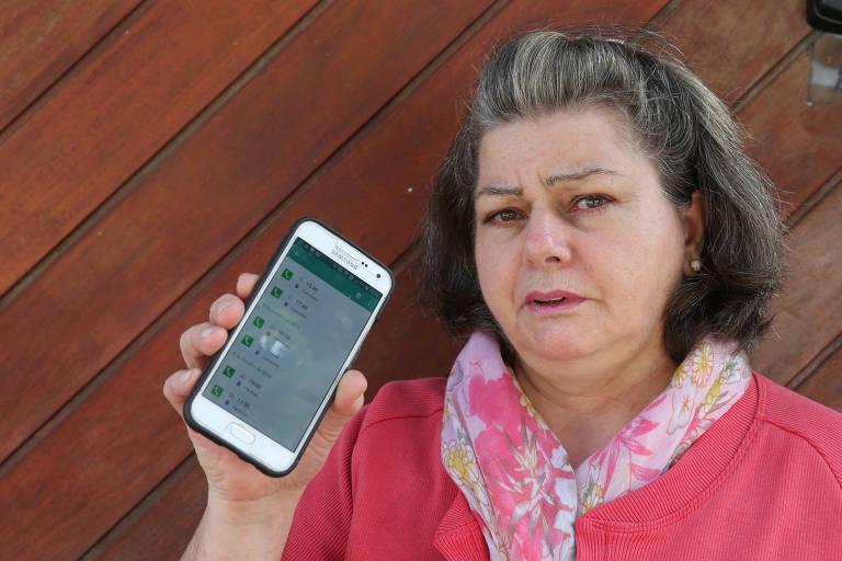 Aposentada mostra telefone celular