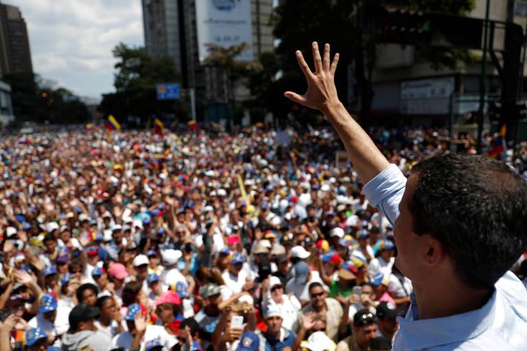 O líder opositor Juan Guaidó sinaliza para manifestantes durante protesto em Caracas neste sábado (6)